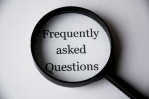 Lente di ingrandimento con scritta Frequently Asked Questions